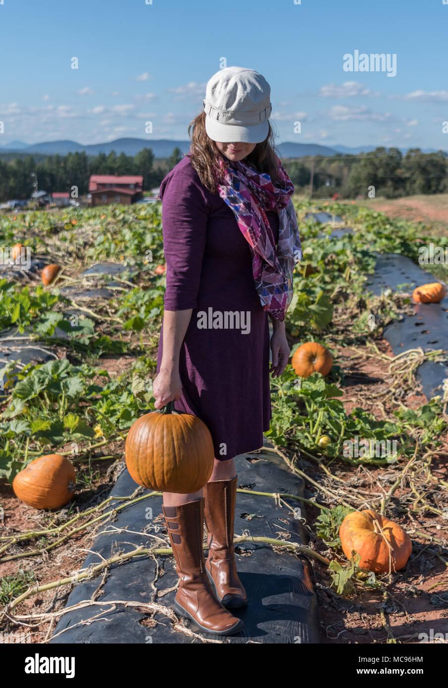 Woman Swings Pumpkin on Sunny Afternoon in pumpkin patch - Stock Image