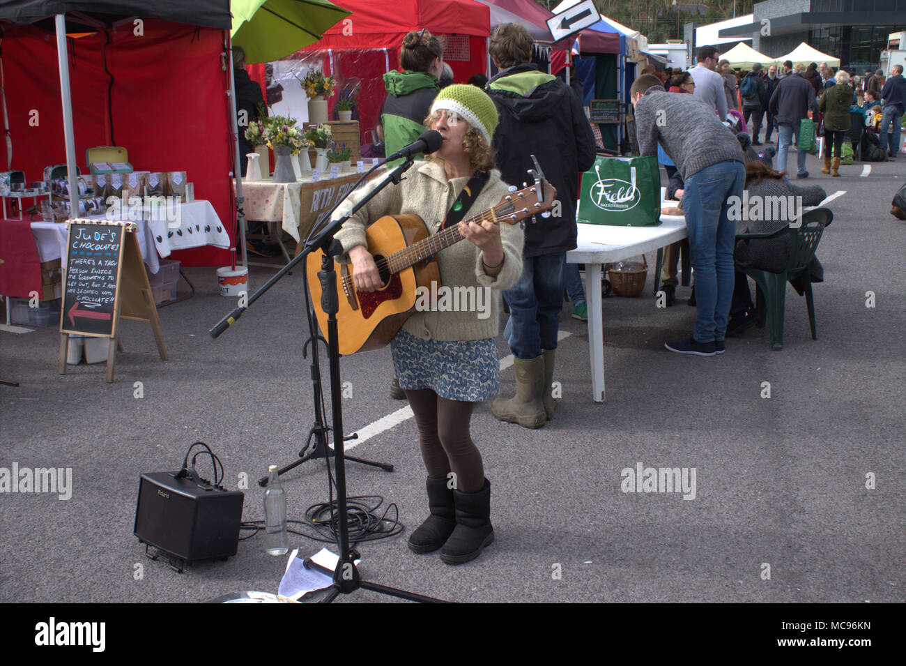 female-busker-playing-a-guitar-on-the-street-at-a-local-country-market-in-skibbereen-west-cork-ireland-a-popular-tourist-and-holiday-makers-town-MC96KN.jpg
