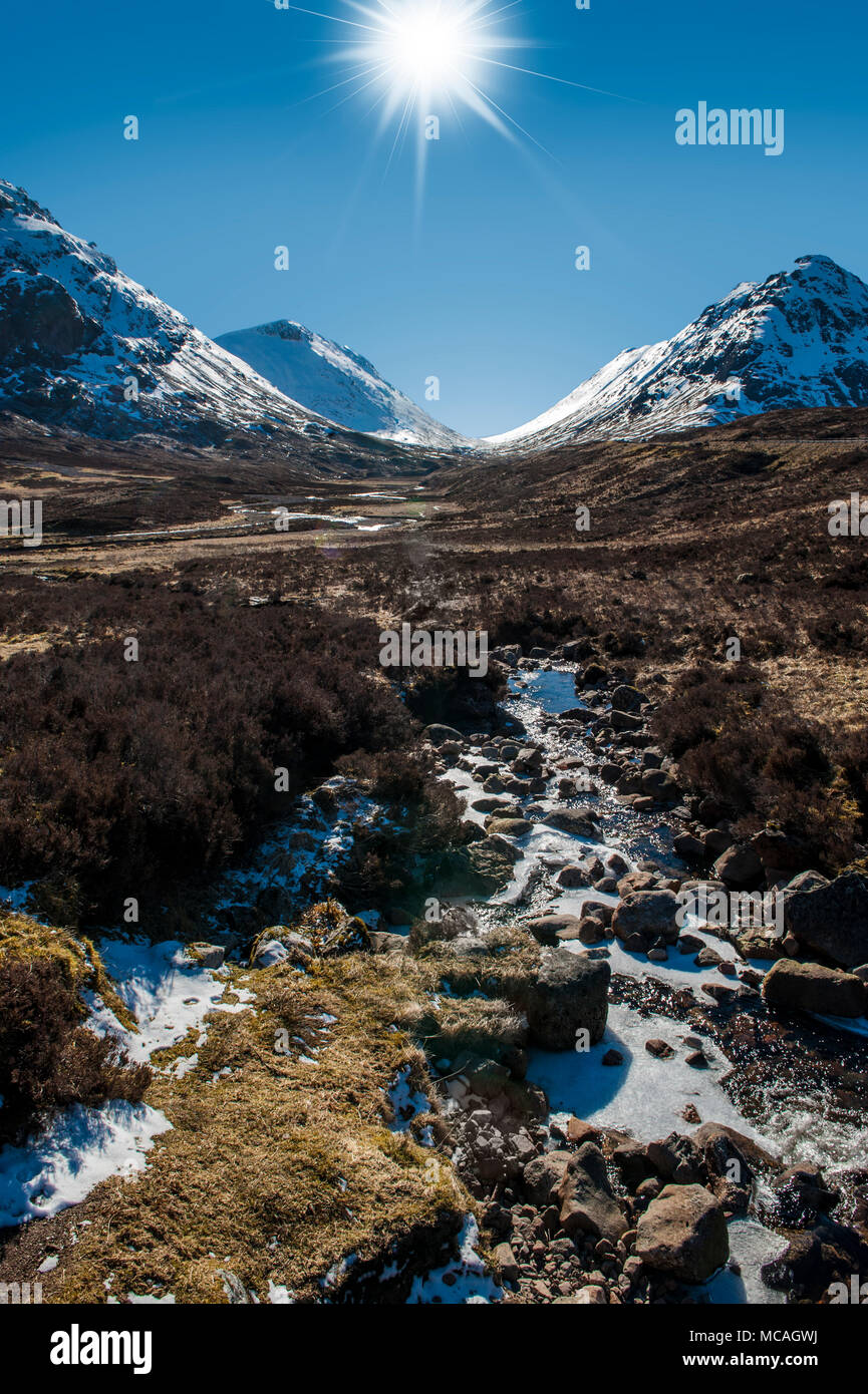 Breathtaking views of the Scottish Highlands - a bright sunshine shines down on the beautiful mountains of Glencoe - Stock Image