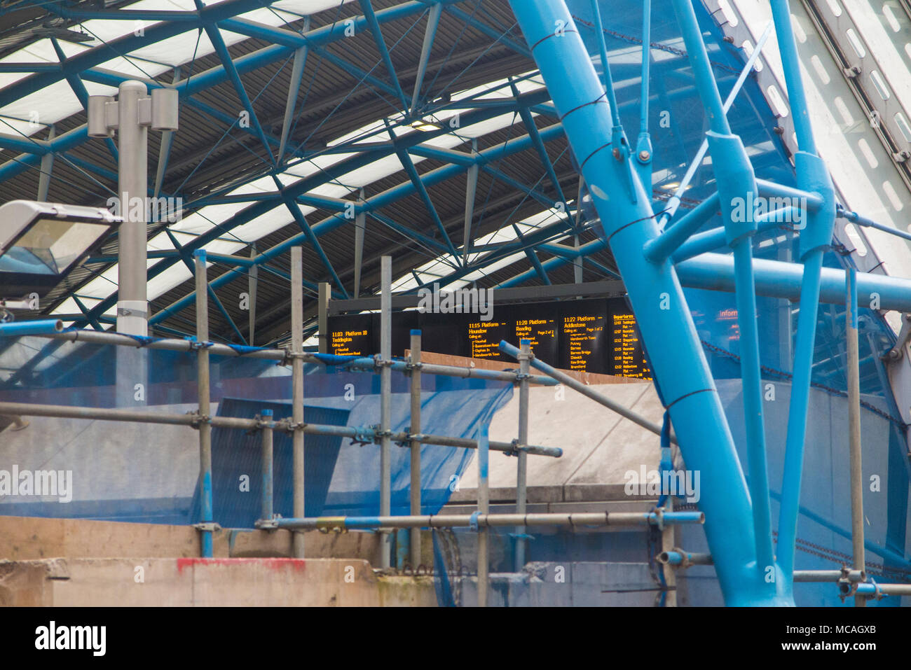 Work continues on the Waterloo International station conversion, with scaffolding and work but platforms and train displays fully operational - Stock Image