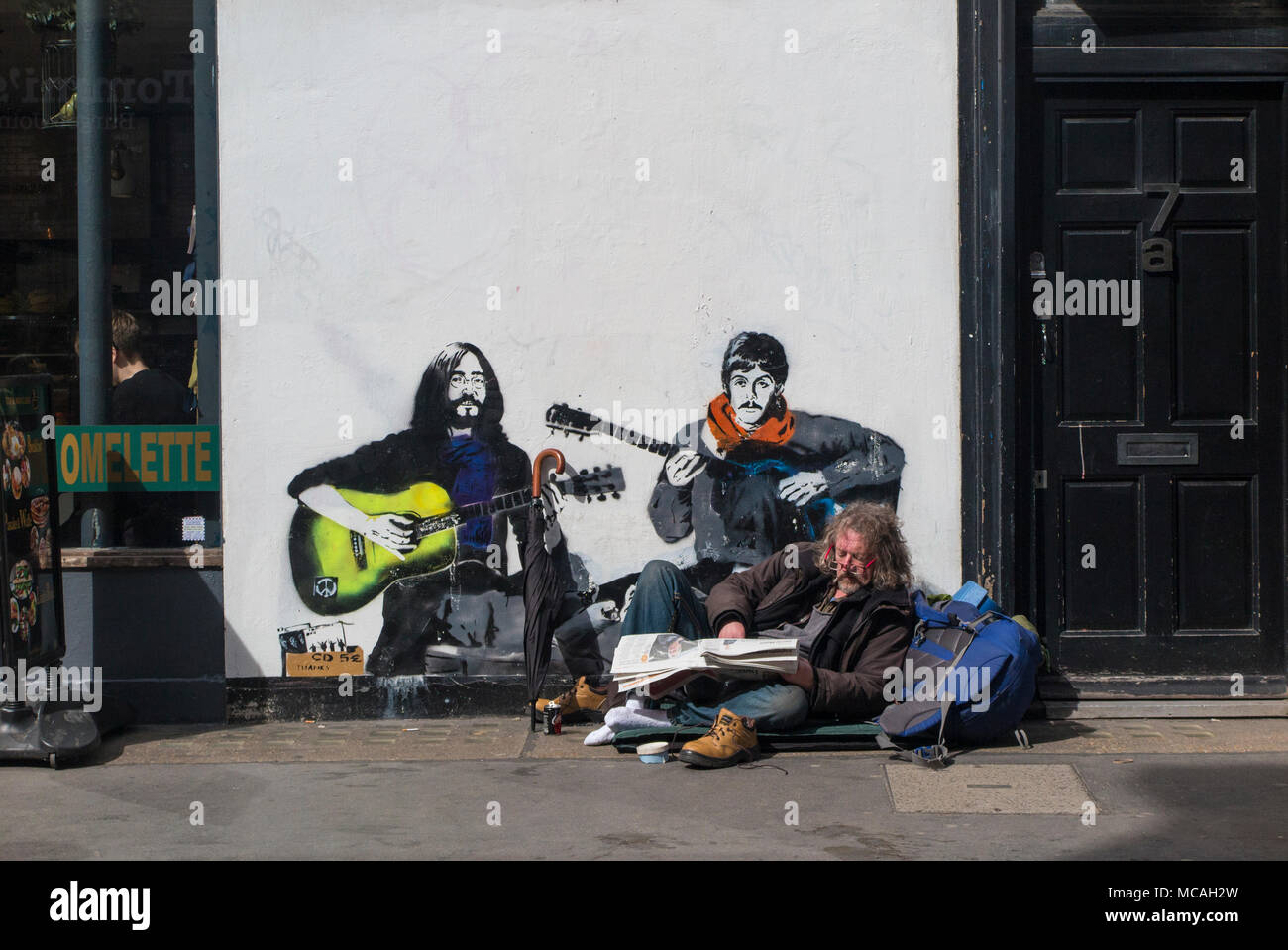 A man relaxes on the pavement in Soho in front of a picture of John Lennon and Paul McCartney - Stock Image