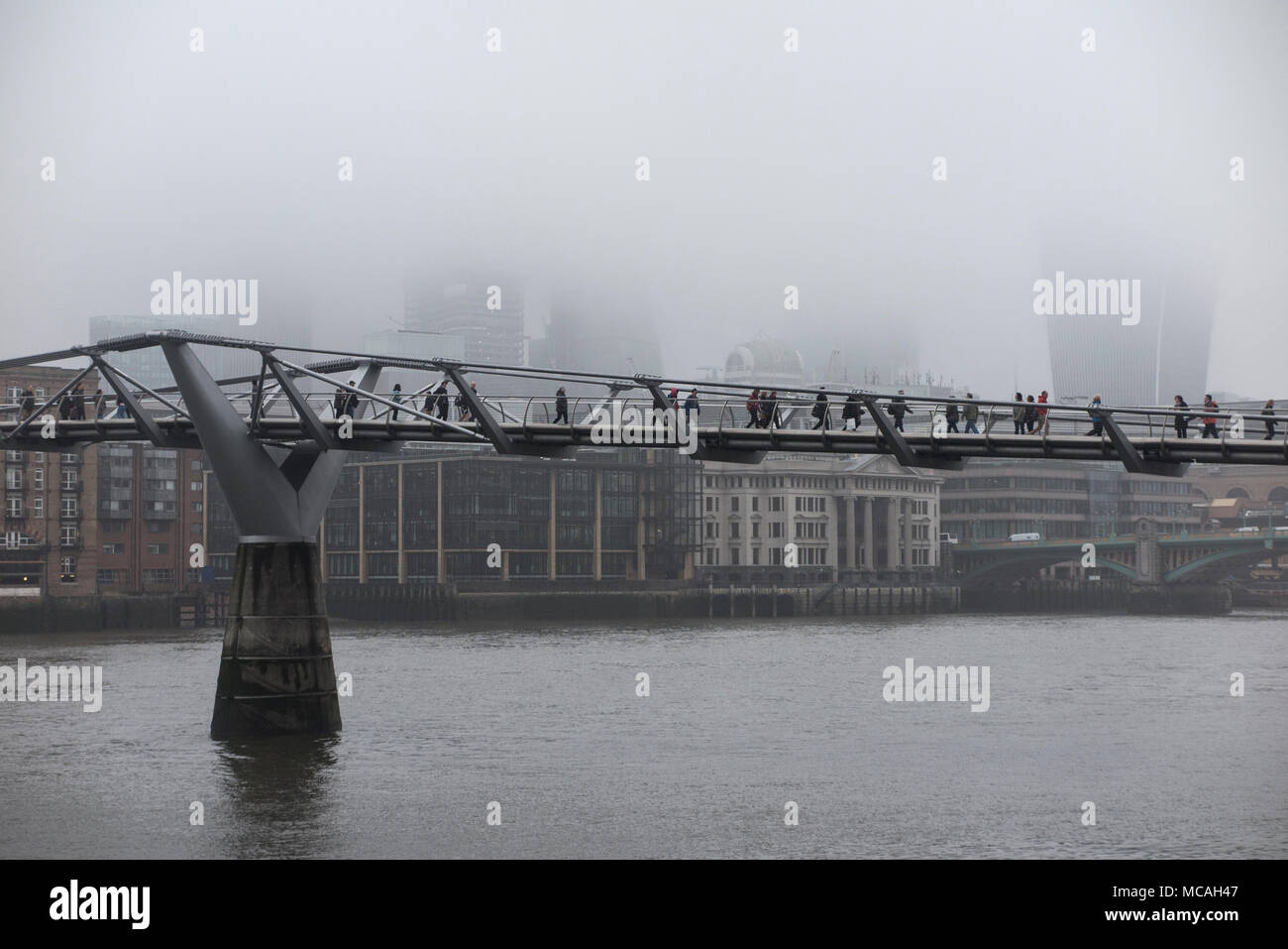 a gloomy, misty day in London with the skyscrapers shrouded in mist and fog whilst commuters and tourists walk over the Millennium bridge - Stock Image