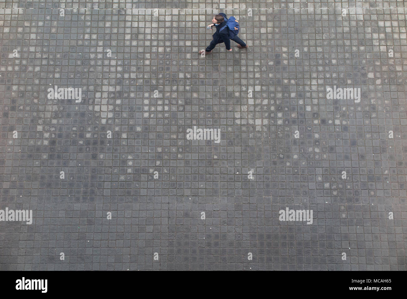 Looking down from high above on a pedestrian taking wide steps, walking along a cobbled pavement - Stock Image