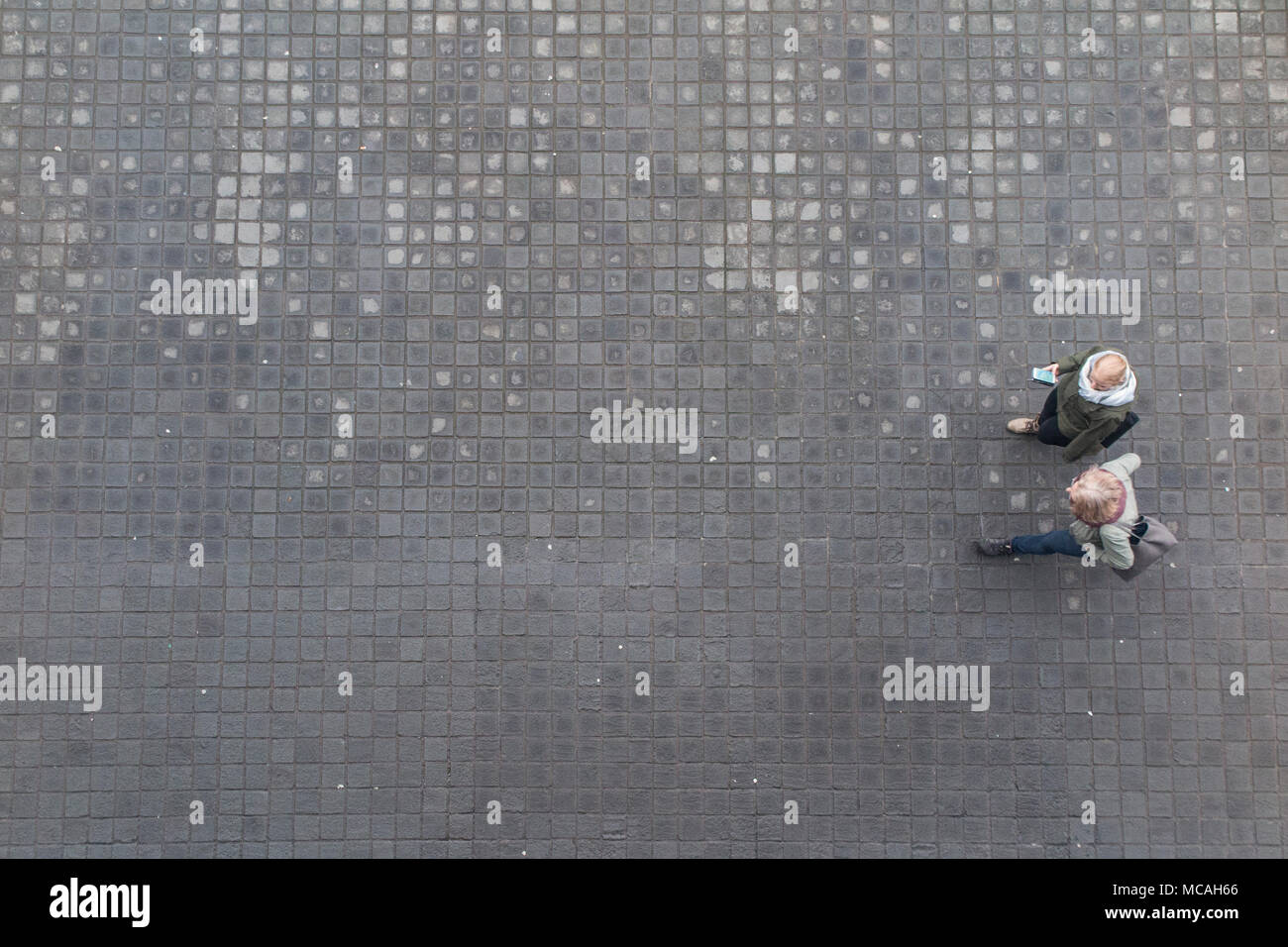 Looking down from high above on two pedestrians, walking along a cobbled pavement - Stock Image
