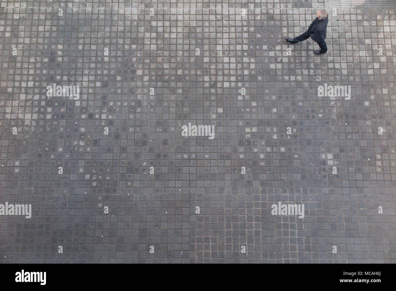 Looking down from high above on a pedestrian, walking along a cobbled pavement - Stock Image
