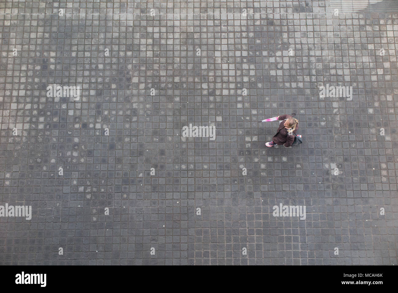 Looking down from high above on a female pedestrian, walking along a cobbled pavement with an umbrella - Stock Image