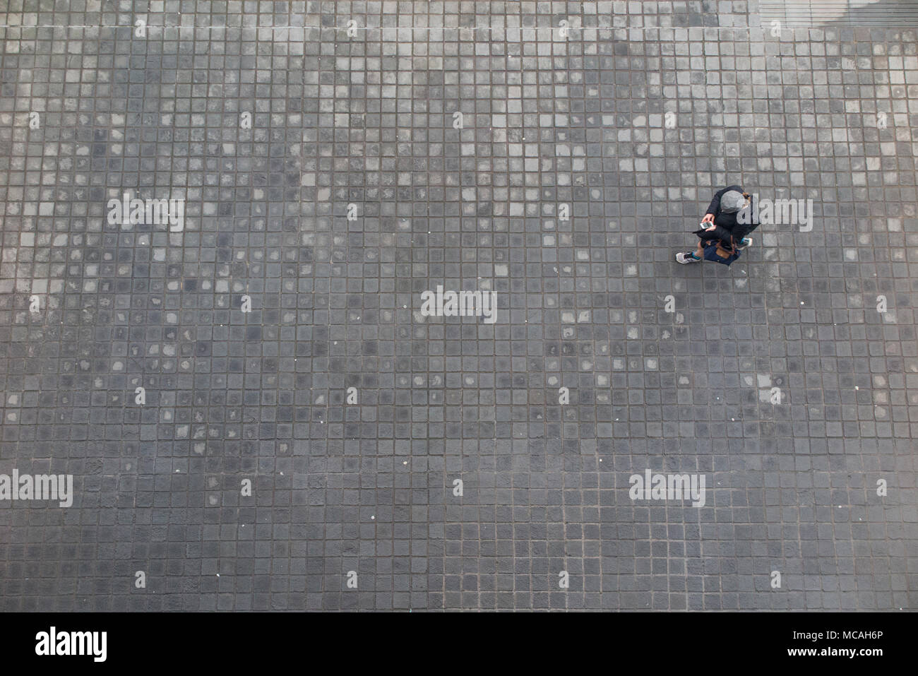 Looking down from high above on a pedestrian who is checking their mobile phone whilst walking along a cobbled pavement - Stock Image