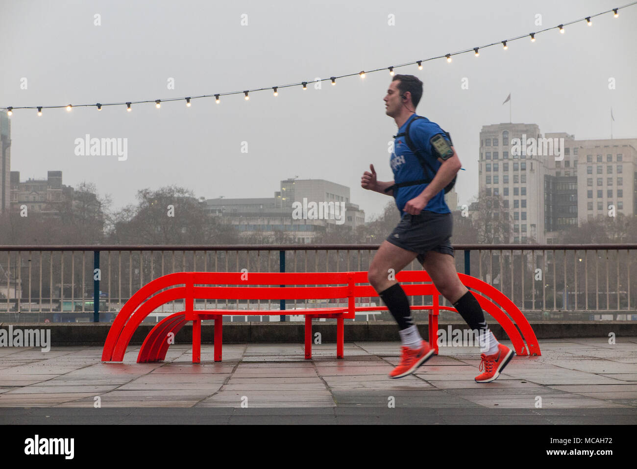 A man runs along the South Bank in front of a Jeppe Hein orange bench -part of the Modified Social Bench project and a string of lights on a grey day - Stock Image