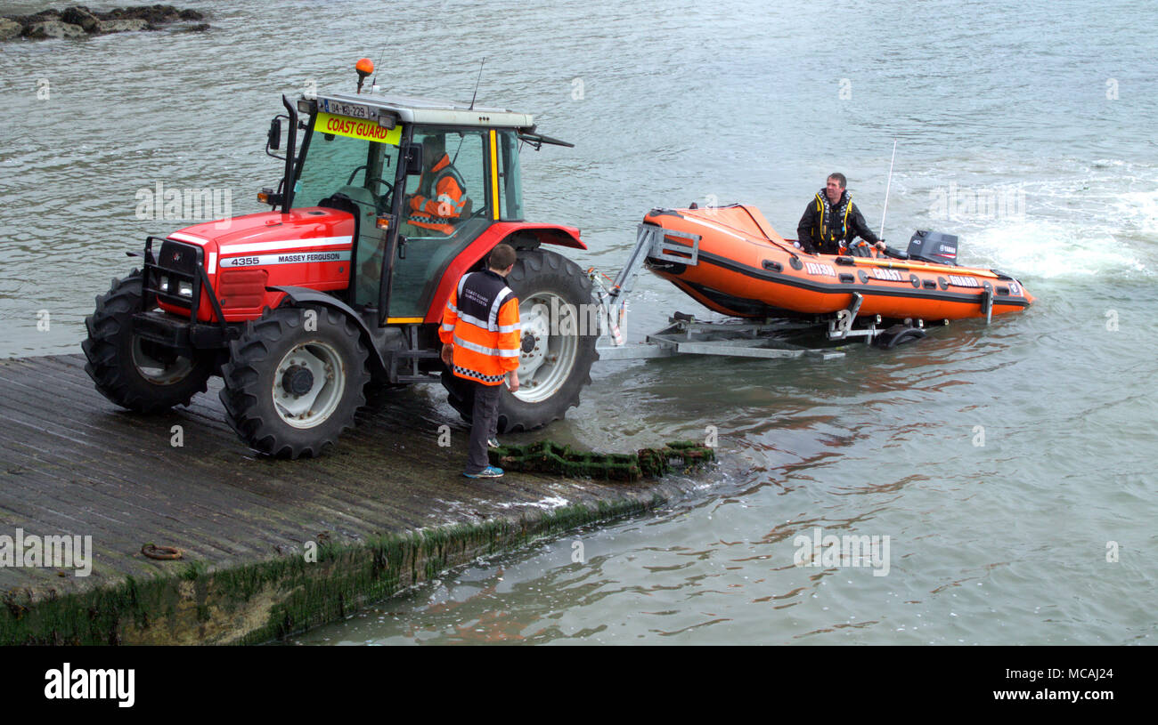 irish-coast-guard-landing-their-small-inshore-lifeboat-onto-a-trailer-and-being-hauled-up-the-slipway-by-a-massey-ferguson-tractor-MCAJ24.jpg