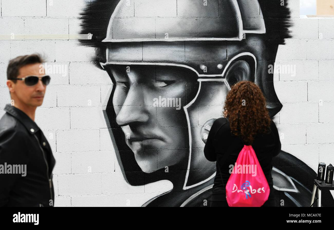 Guadalajara, Guadalajara of Spain. 14th Apr, 2018. People stand in front of a graffiti in Driebes, Guadalajara of Spain, on April 14, 2018. The village of Driebes held a contest of graffiti to call the public attention to its depopulation issue. The population of Driebes decreased by more than 67 percent in five decades, from some 1,200 to 390 inhabitants. Credit: Guo Qiuda/Xinhua/Alamy Live News - Stock Image