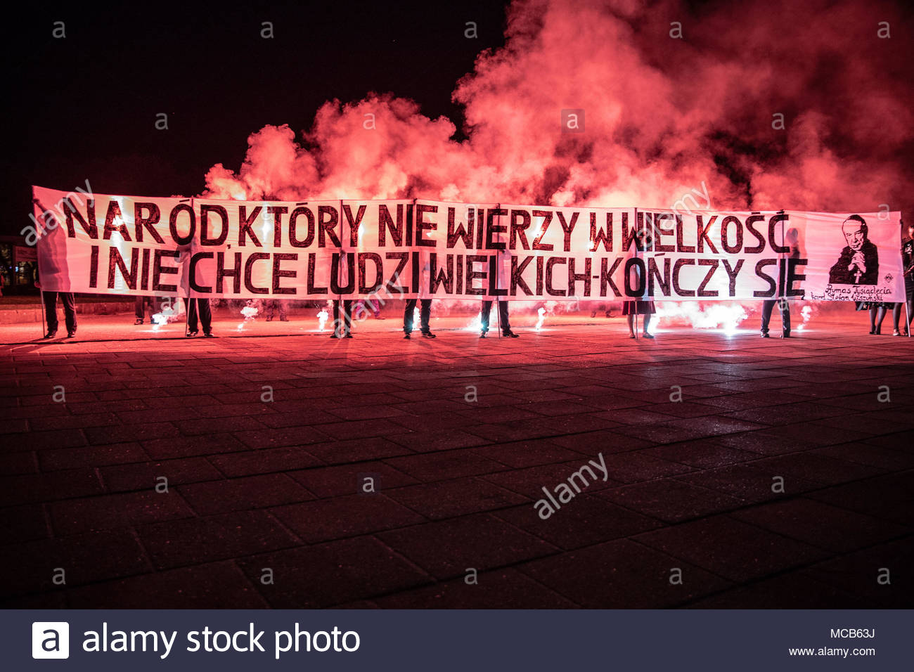 Czestochowa, Poland. 14th Apr, 2018. People hold banner and burn flares as far-right nationalists belonging to the All-Polish Youth organization take part in a torch-lit 'pilgrimage' at Jasna Gora Monastery, in Czestochowa on April 14, 2018. Its agenda proclaims that its aim is to raise Polish youth in a Catholic and patriotic spirit. Currently it plays main role as part of the National Movement party. (c) copyright Credit: CrowdSpark/Alamy Live News - Stock Image