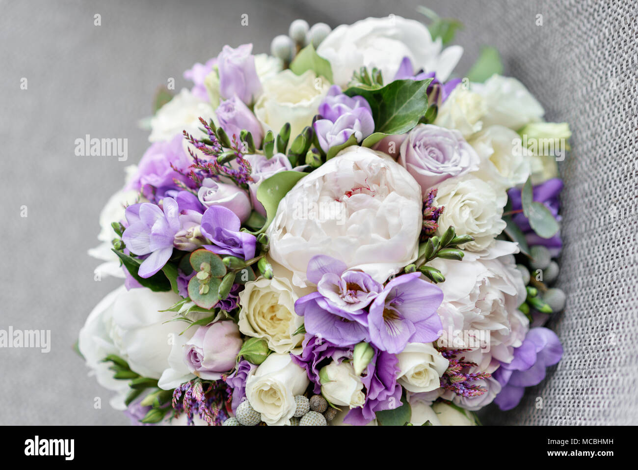 Brides wedding bouquet with peonies, freesia and other flowers on ...