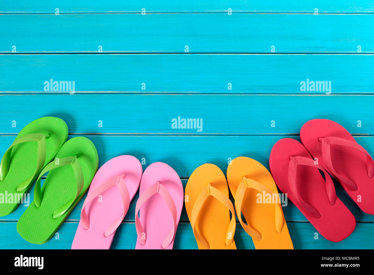 3b3715dd819 Row of colorful flip flops on old weathered blue painted beach decking.  Space for copy.
