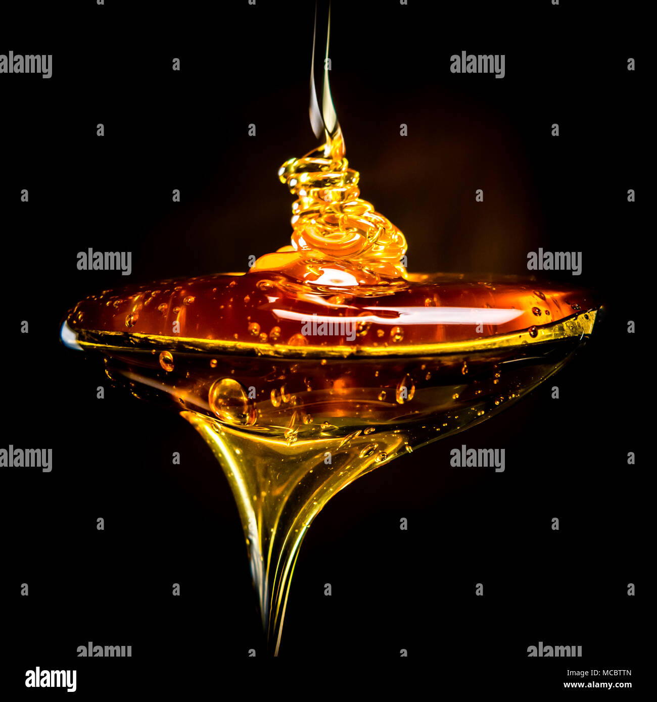 Abstract of Honey Pouring Into Spoon - Stock Image