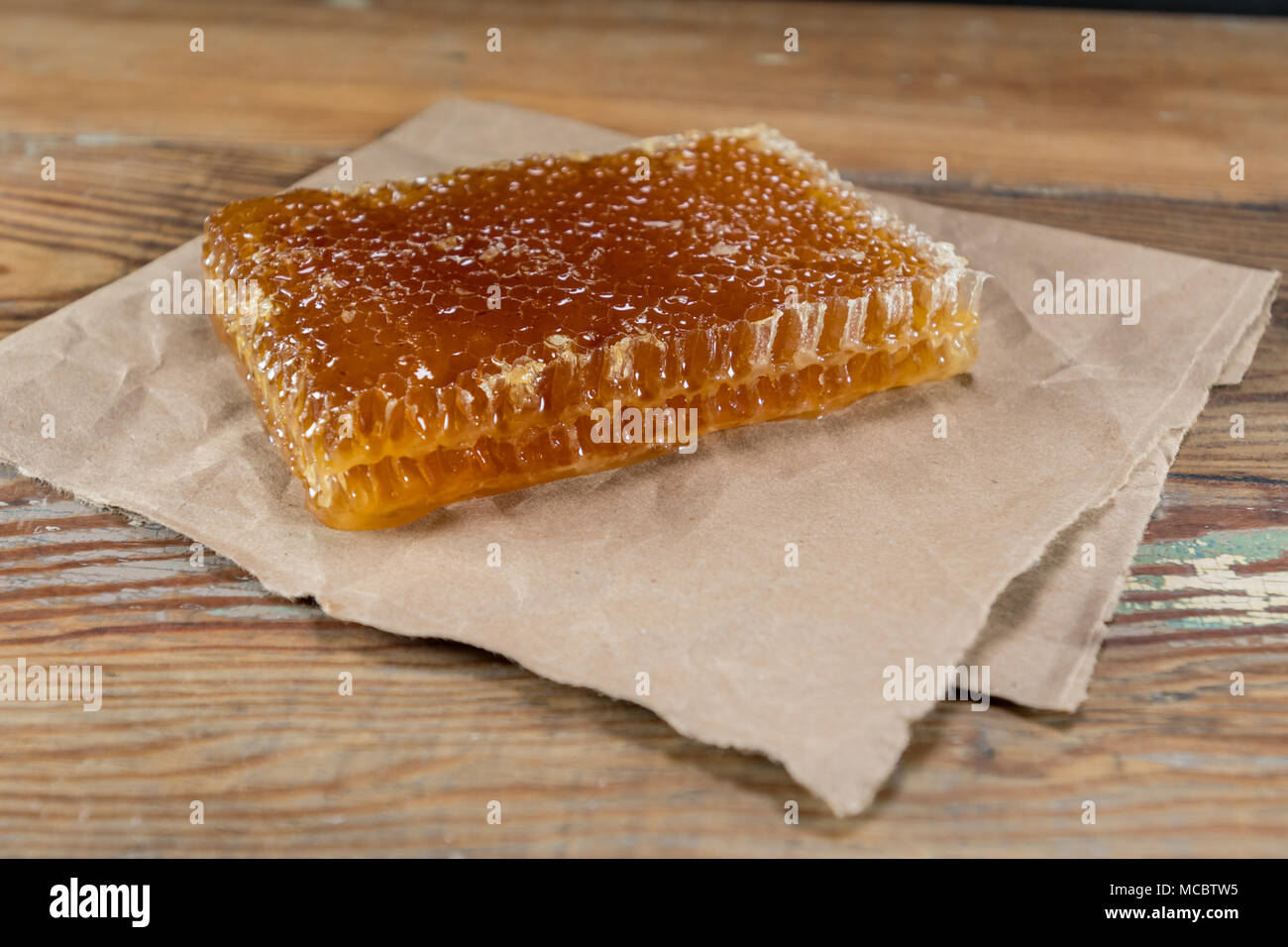 Angle View of Honey Comb on Brown Paper on wooden table - Stock Image