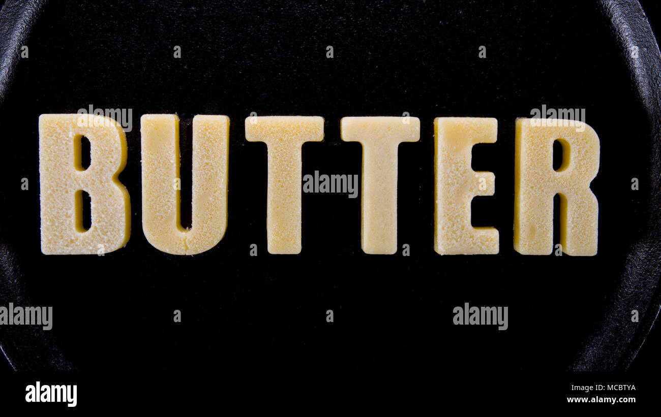 Butter Words Butter on cast iron skillet background - Stock Image