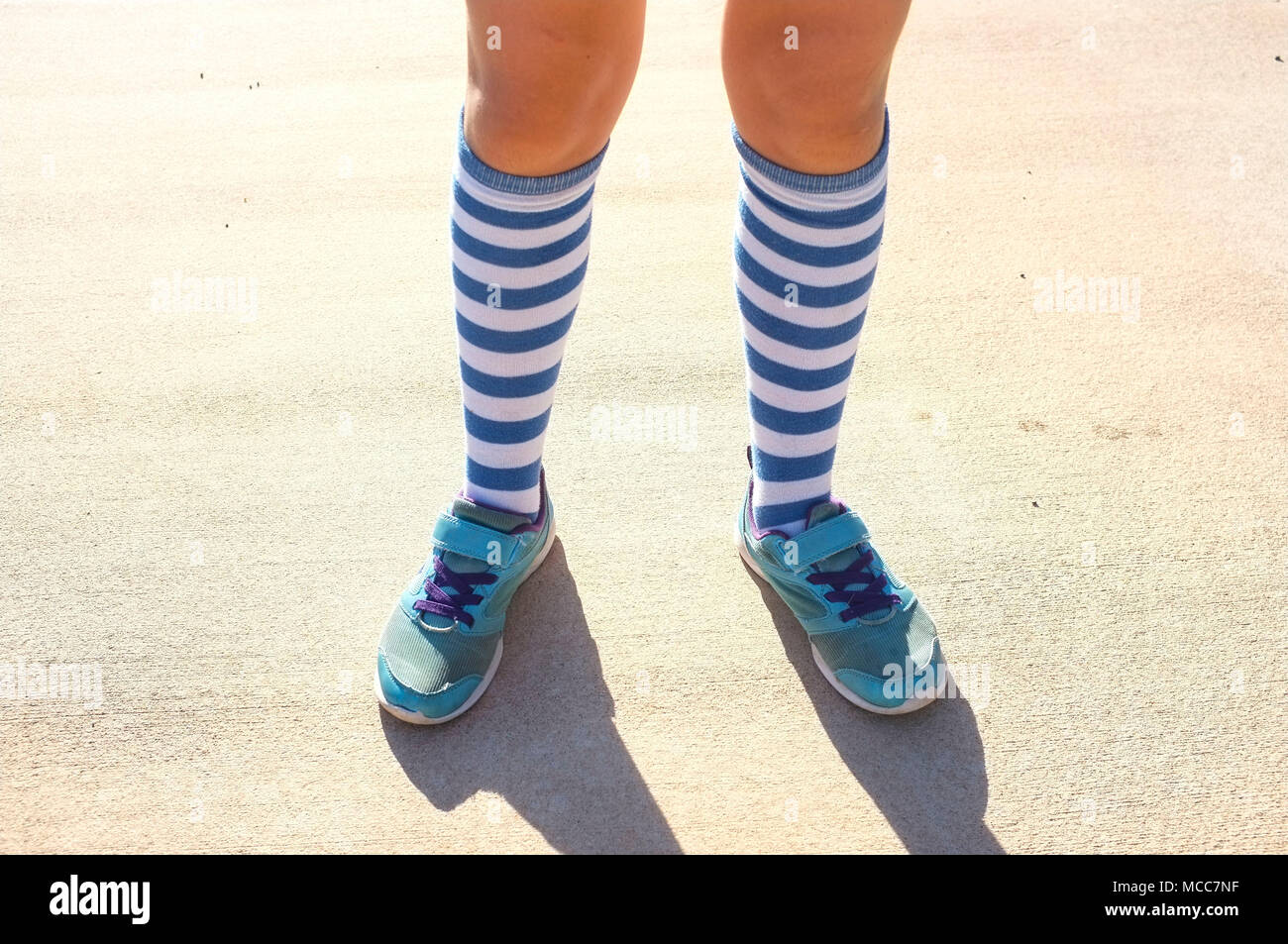 lower-legs-of-a-young-girl-wearing-sport-shoes-and-long-striped-socks-MCC7NF.jpg
