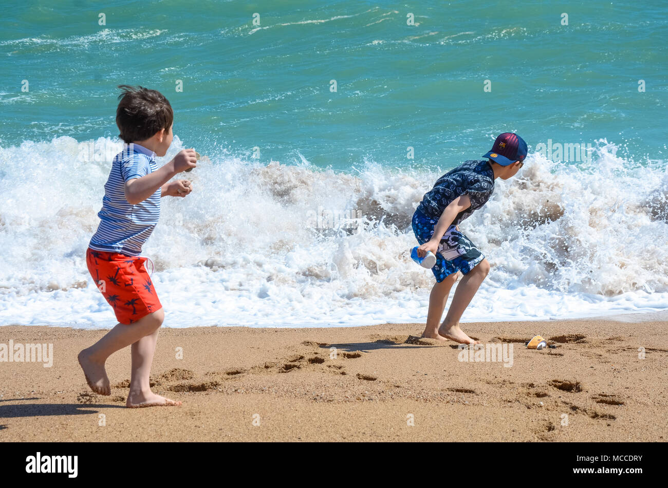two-young-brothers-play-together-on-a-sandy-beach-close-to-the-waters-edge-MCCDRY.jpg