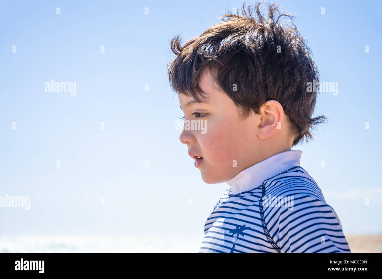 a-portrait-of-a-young-boy-taken-outside-against-a-clear-blue-sky-while-on-holiday-MCCE0N.jpg