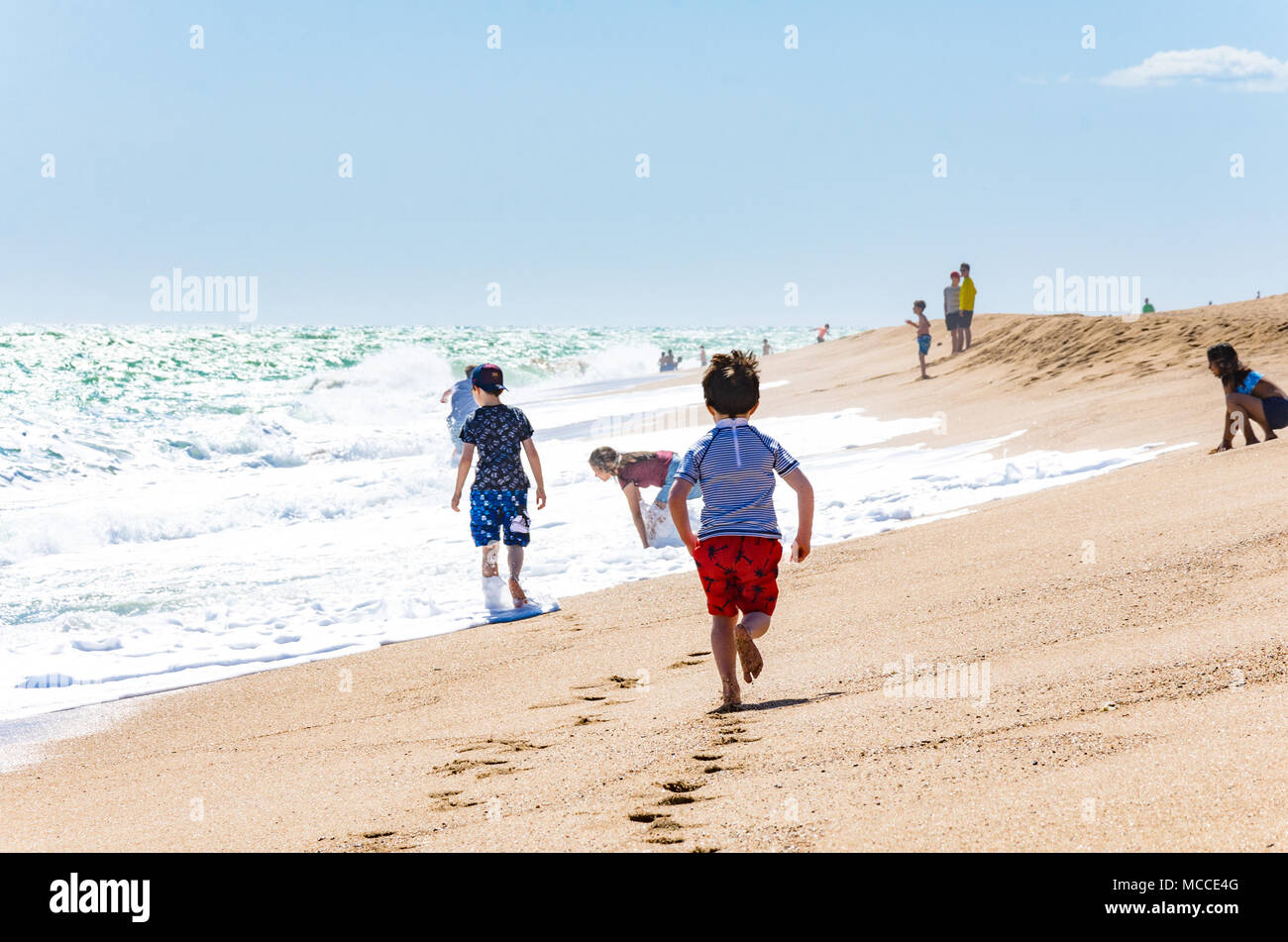 a-young-boy-runs-along-a-beach-close-to-the-waters-edge-where-the-waves-roll-in-on-the-sand-MCCE4G.jpg