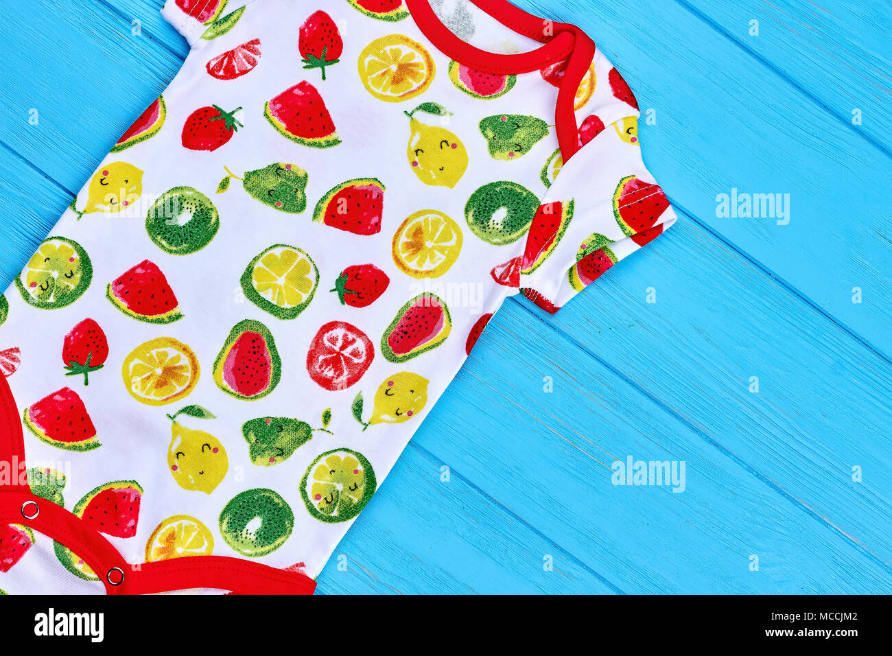 10bbd52f46d Close up of natural cotton bodysuit. Fruit print brand romper for newborn  on blue woode background. Kids brand outfit.