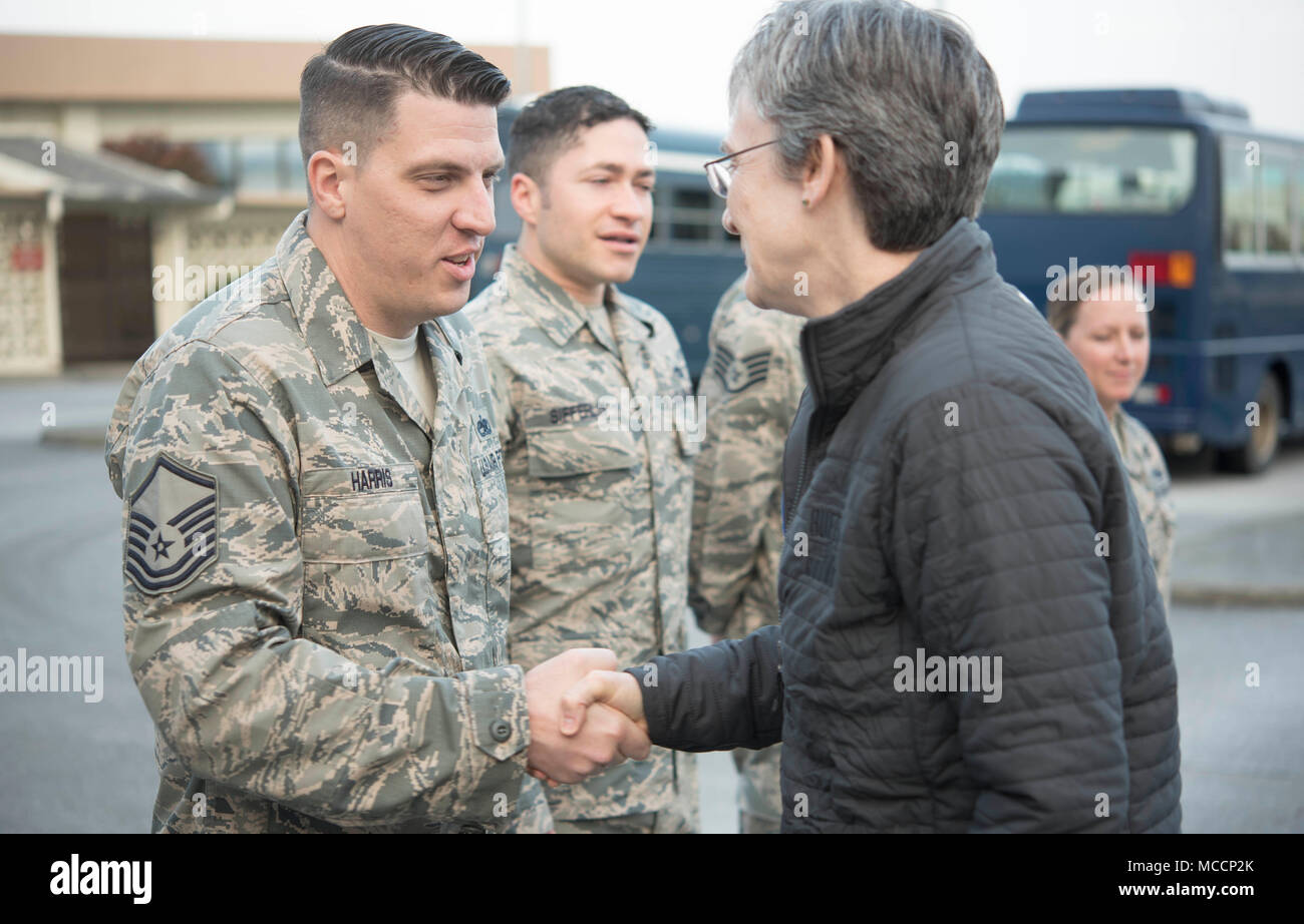 Secretary of the Air Force Heather Wilson coins U.S. Air Force Master Sgt. Brian Harris, 18th Wing protocol NCO in charge, Feb. 2, 2018, at Kadena Air Base, Japan. Challenge coins are a military tradition in which a senior military leader or a member of a distinguished office acknowledges the awards, accomplishments or significant acts of a particular service member. (U.S. Air Force photo by Senior Airman Quay Drawdy) - Stock Image