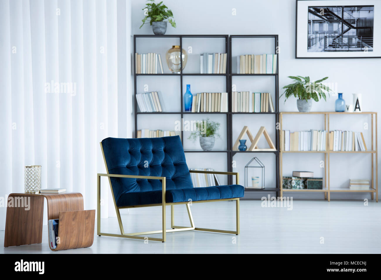 Navy Blue Armchair Next To Wooden Table In Cozy Living Room Interior With Bookshelf And Poster