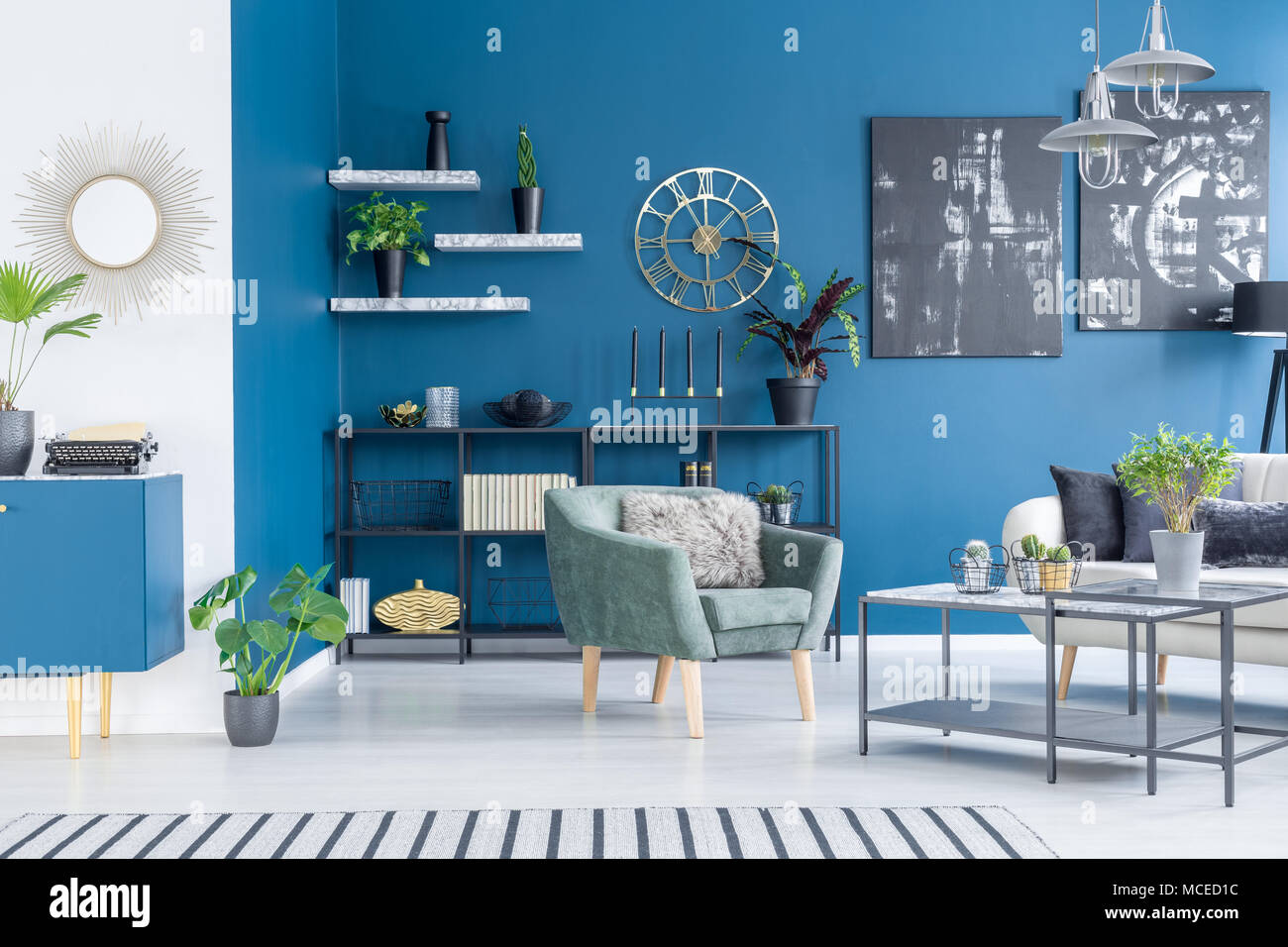 Black paintings on blue wall in modern living room interior with ...