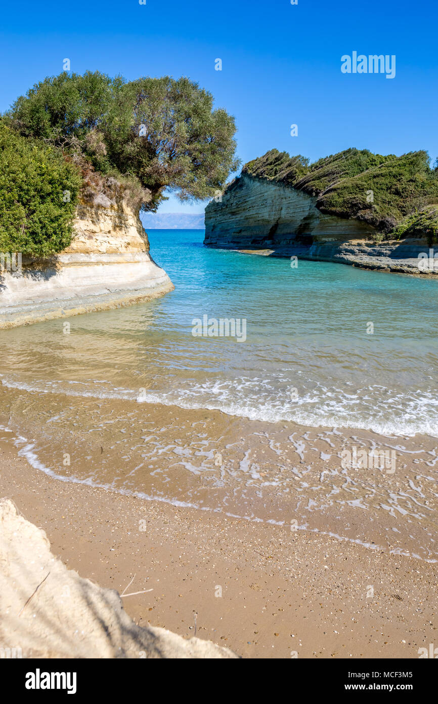 Beautiful dreamy beach with crystal clear blue sea water next to Sidari in Corfu, Greece. Vertical landscape - Stock Image