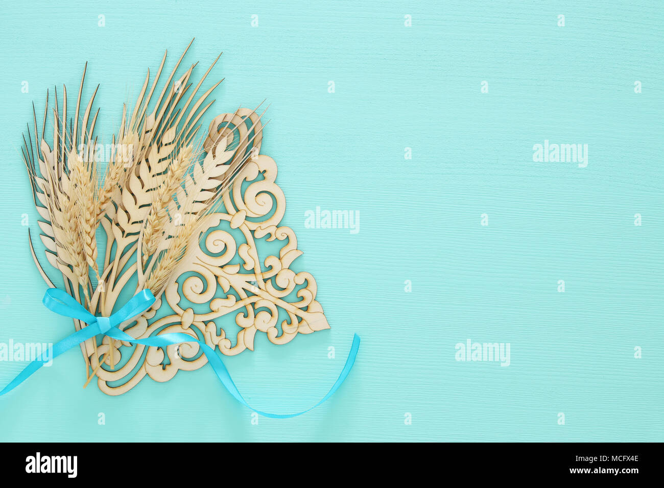 Top View Of Wooden Wheat Crop Decoration Over Mint Background