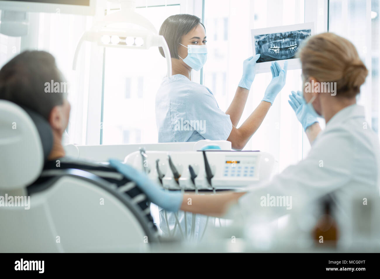 Satisfied dentist discussing work with her colleague - Stock Image