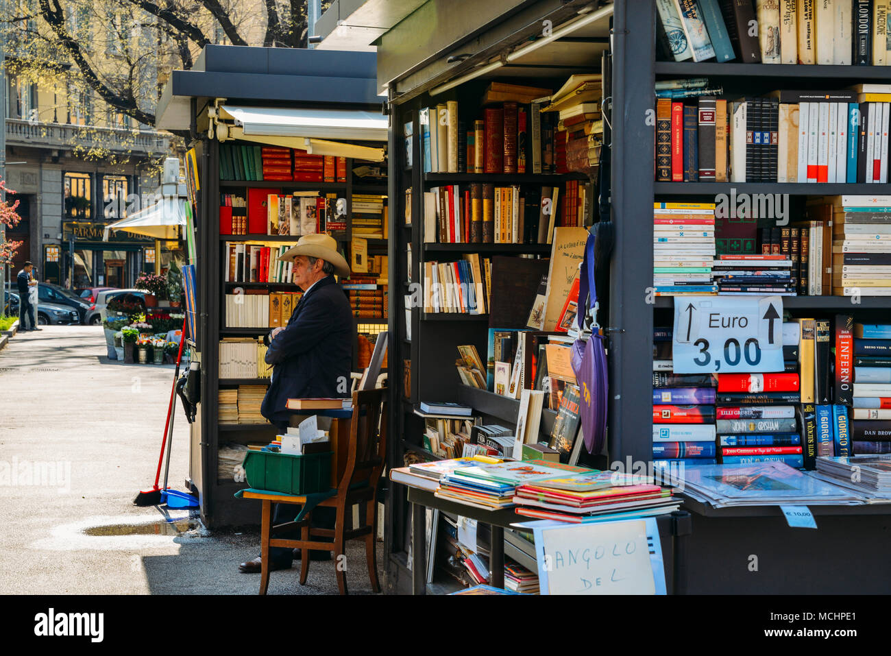 milan-italy-april-14-2018-an-older-man-with-a-cowboy-hat-sells-books-on-the-street-MCHPE1.jpg