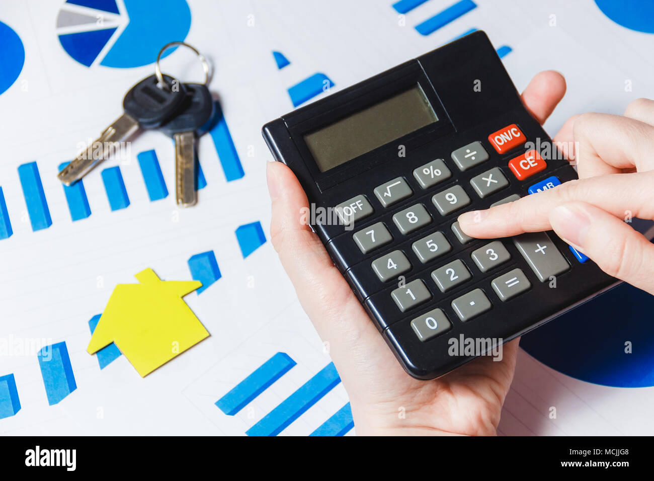 Close up of females hand using calculator with paper house model on close up of females hand using calculator with paper house model on desk with diagram ccuart Gallery