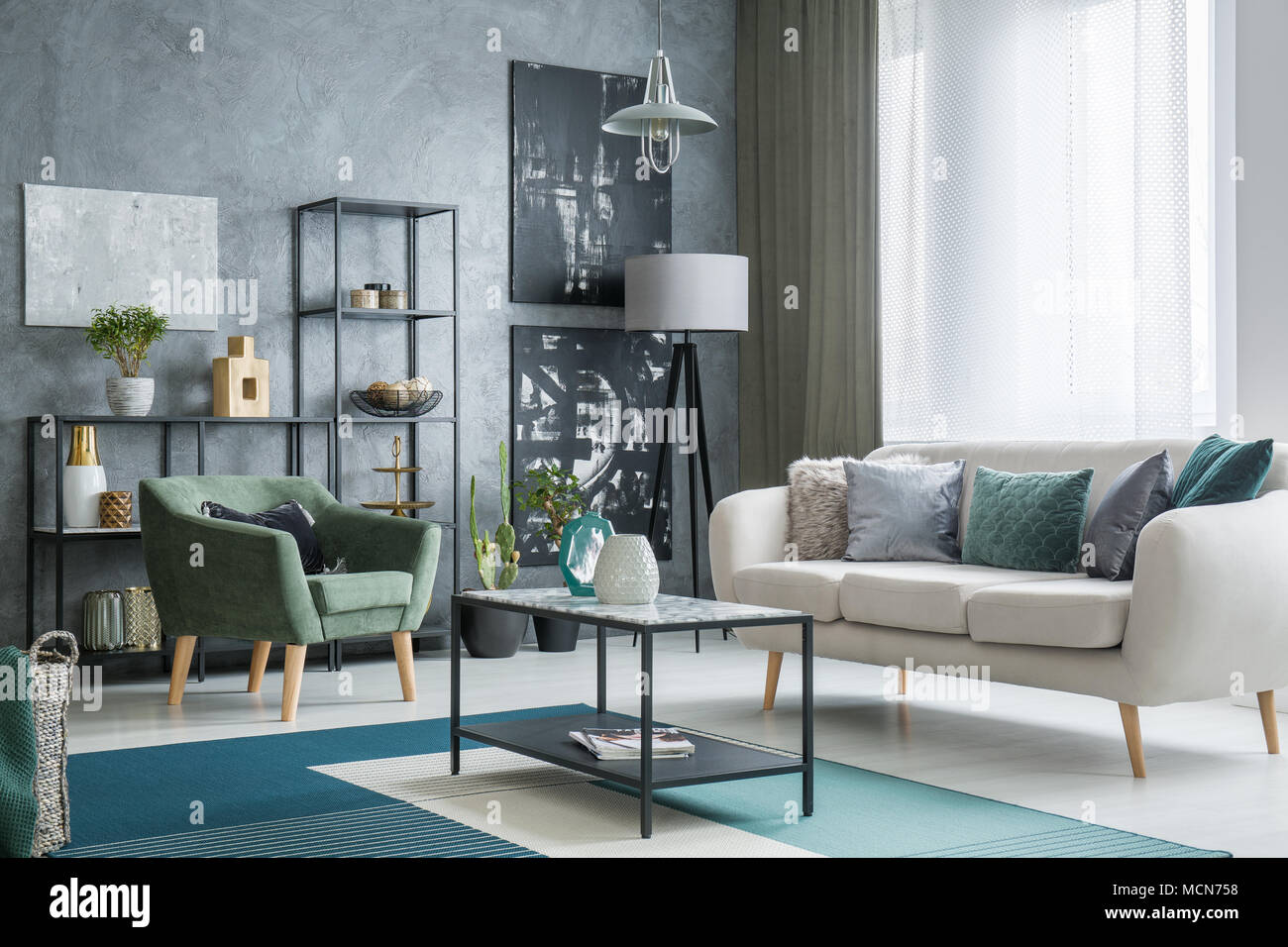 Two Dark Posters Hanging On A Grey Wall In Industrial Living Room Interior  With Lamps, Bright Couch And Table Standing On A Carpet