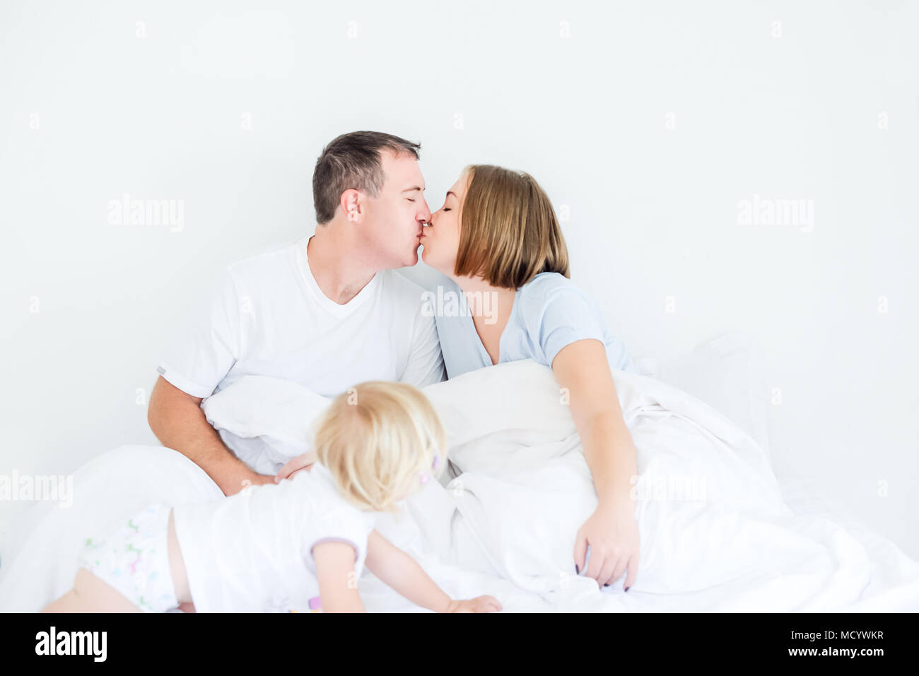 happy and loving family morning concept kissing parents in