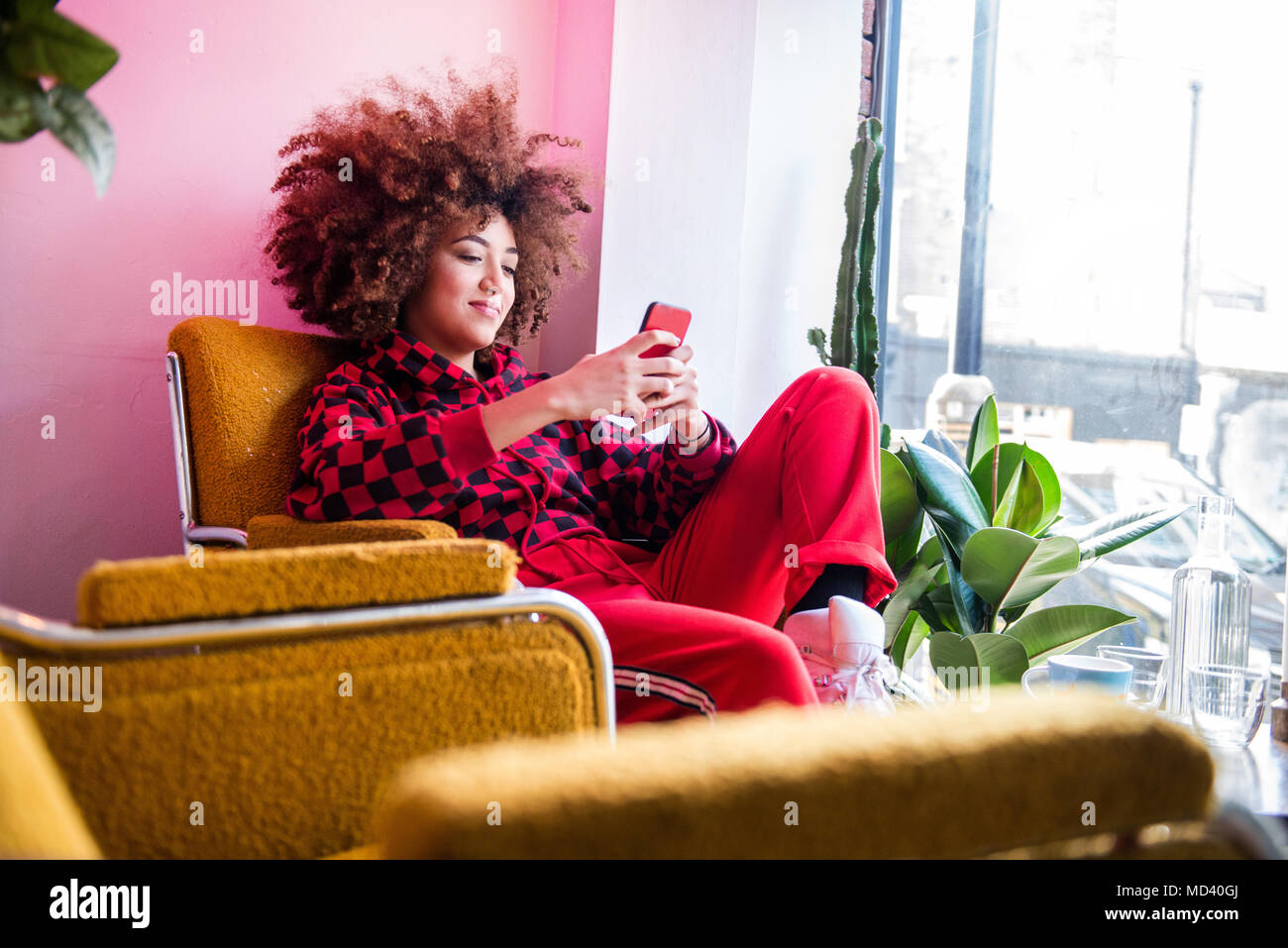 Young woman sitting indoors, using smartphone Stock Photo