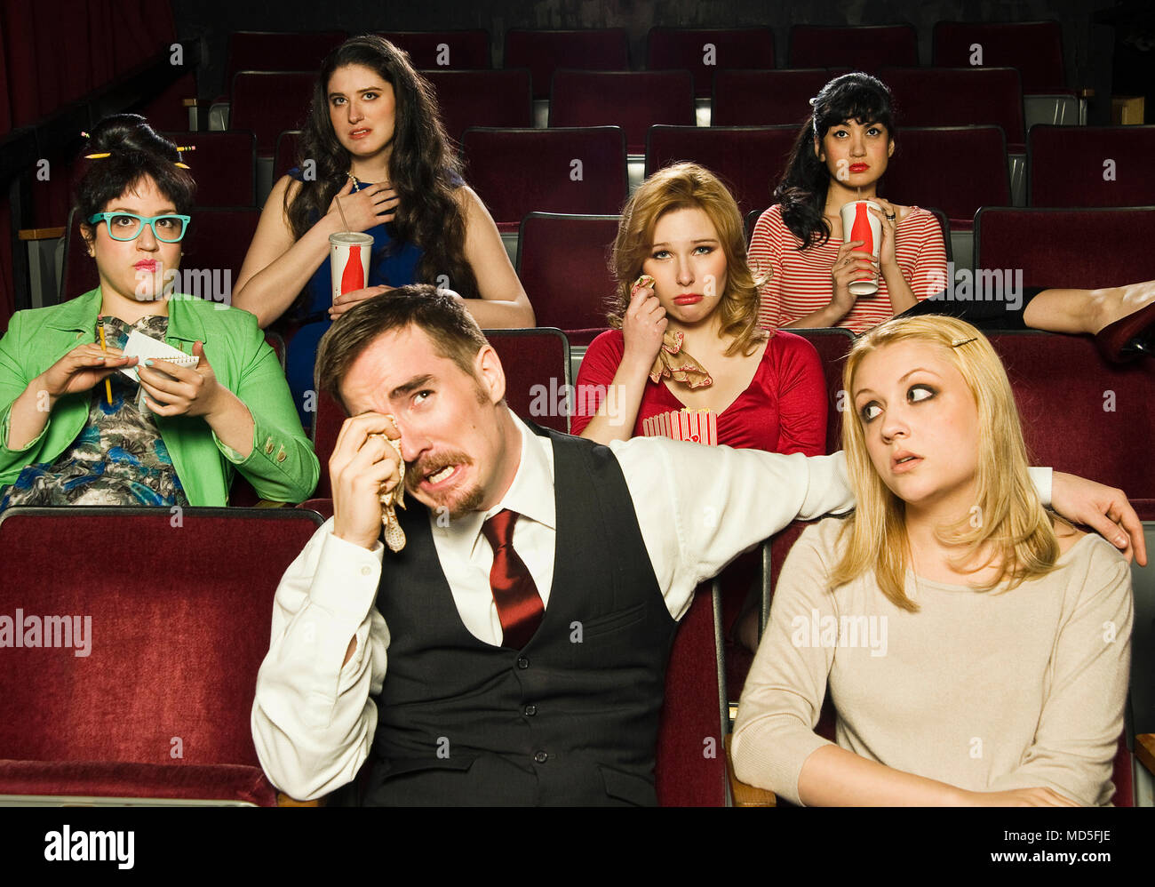 A group of people reacting to a movie in a movie theater. - Stock Image