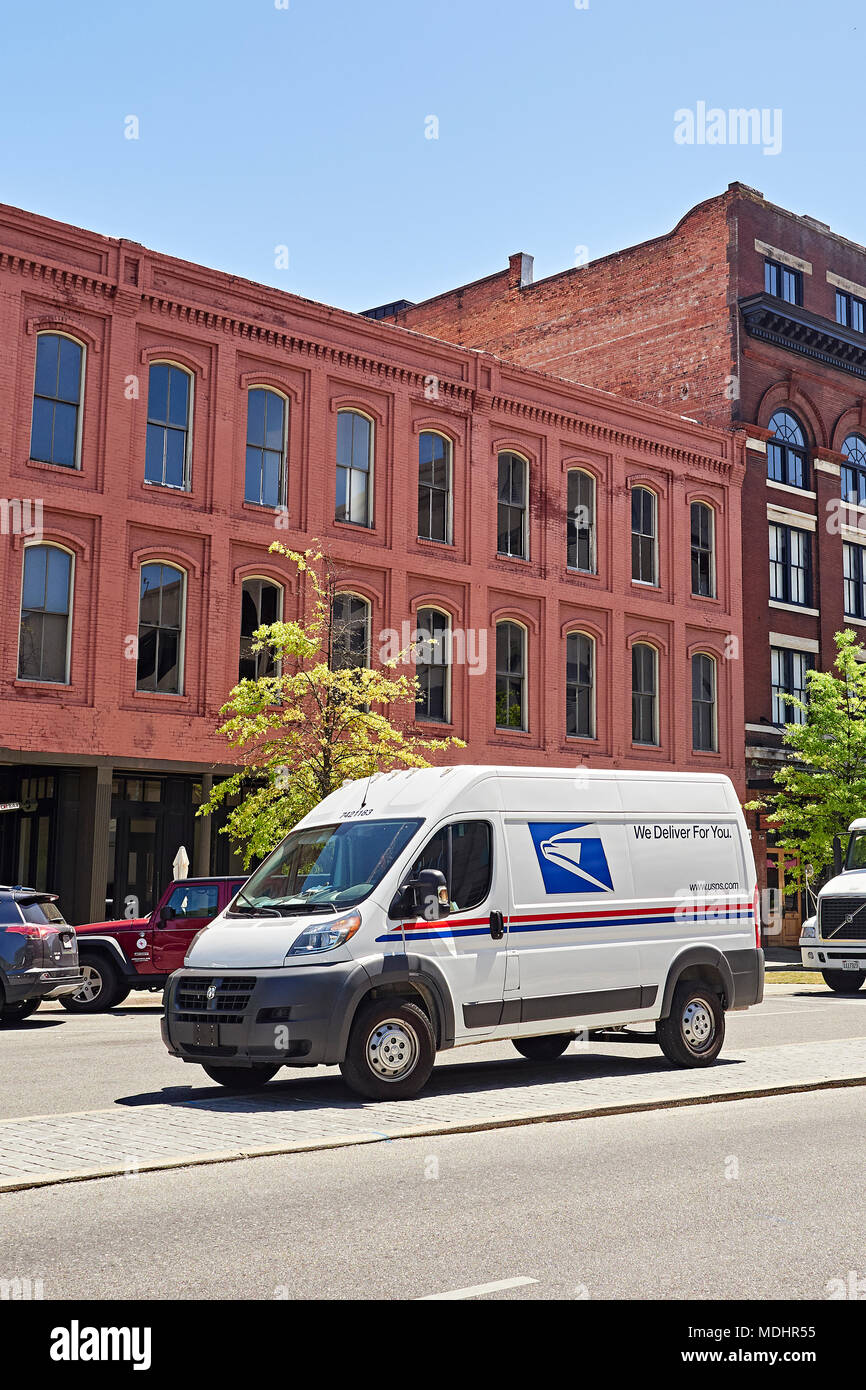 New modern U.S. Postal Service delivery van parked on a city street while the mailman is making deliveries in downtown Montgomery Alabama, USA. - Stock Image
