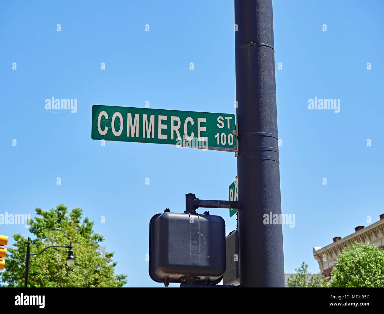 Commerce Street sign overhead on a light pole in downtown Montgomery Alabama, USA indicating the business disctrict. - Stock Image
