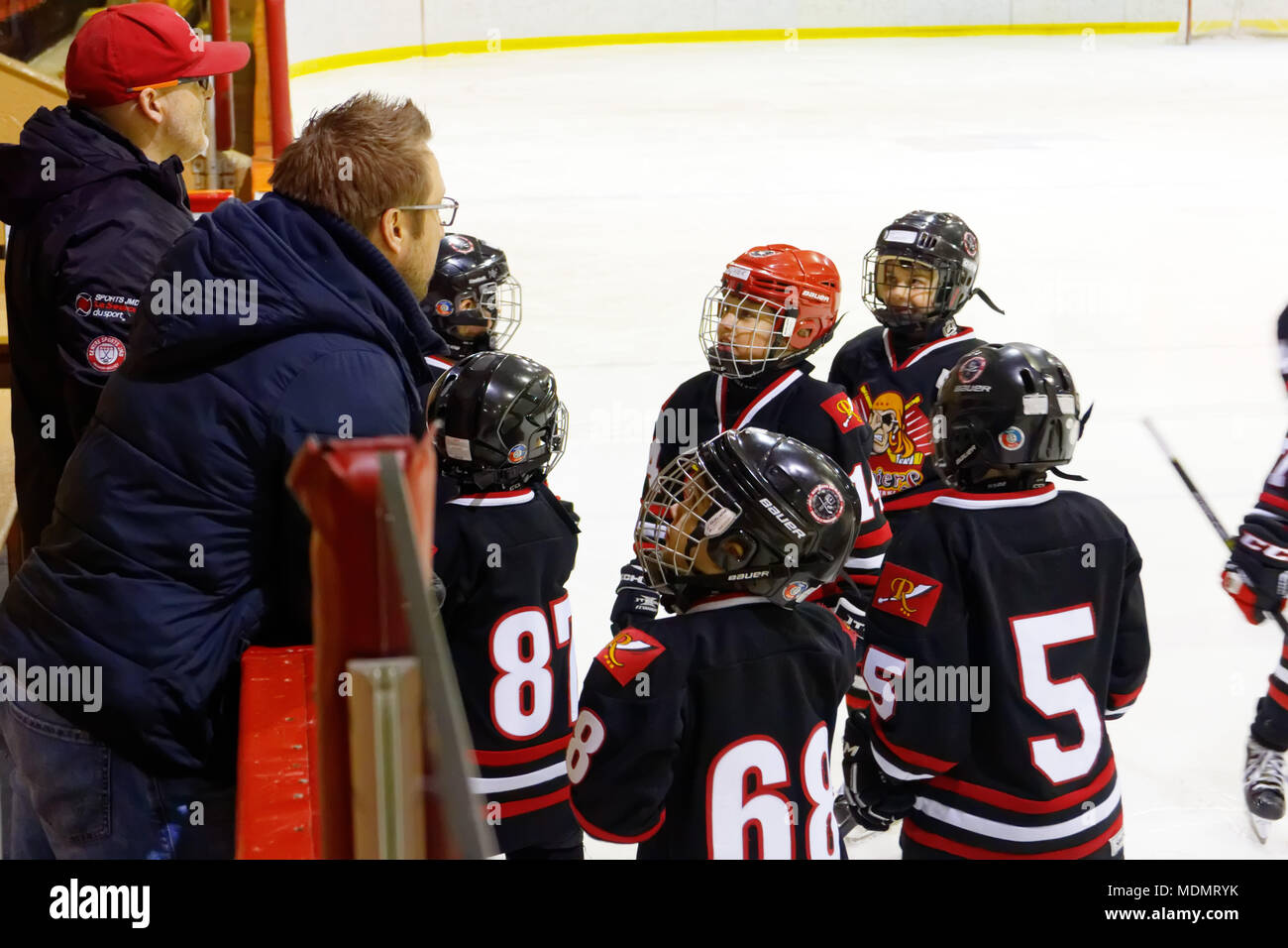 Young ice hockey players being addressed by their coach before a match - Stock Image