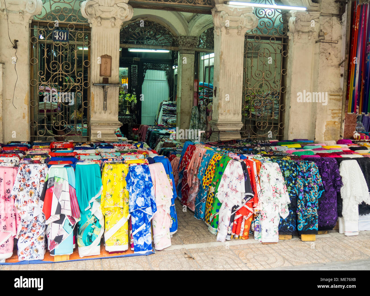 Bolts of fabric on display in a textile market located in a French colonial building in Ho Chi Minh City, Vietnam.Stock Photo