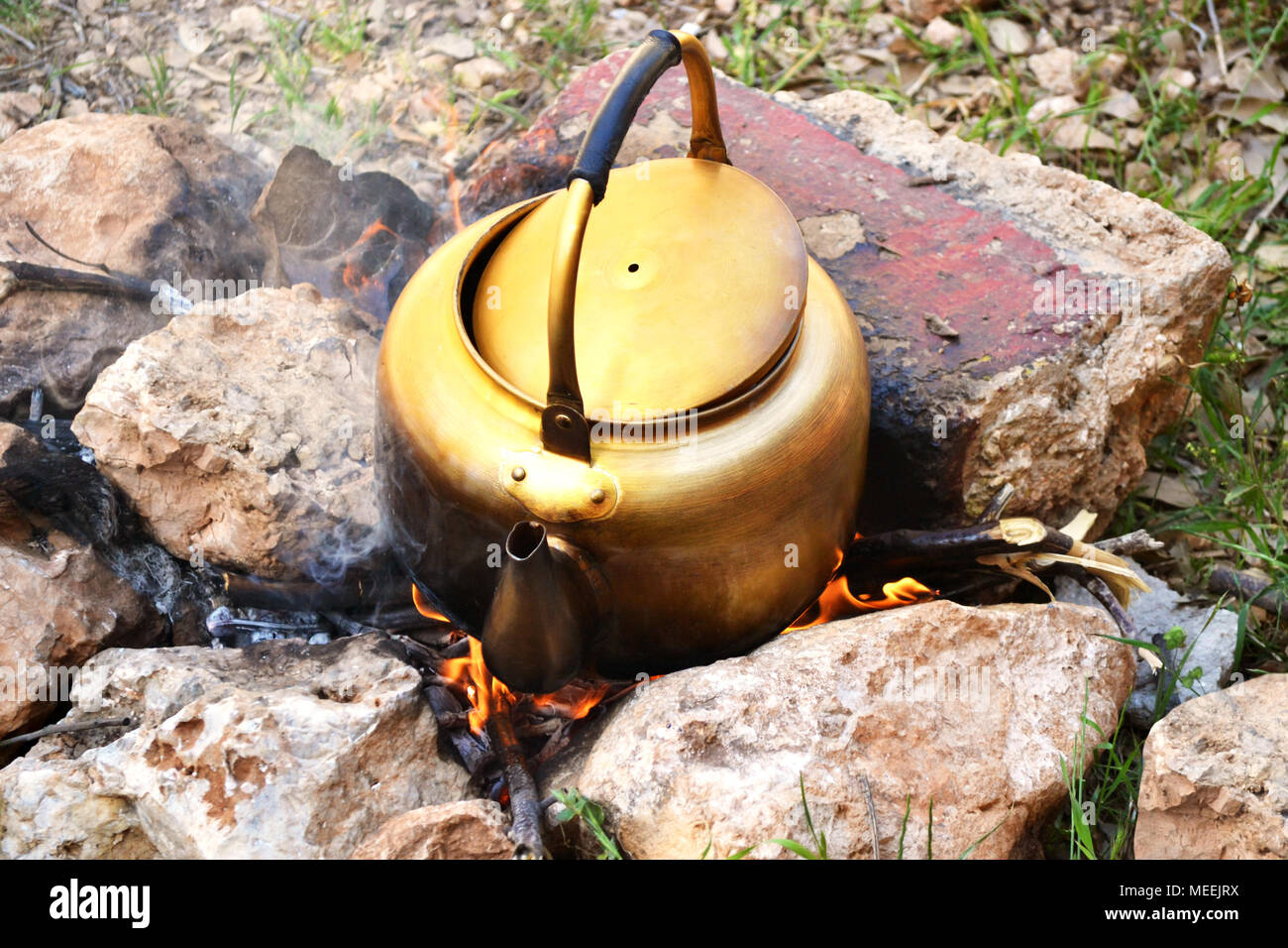 Golden old kettle to boil water on wood fire while camping - Stock Image