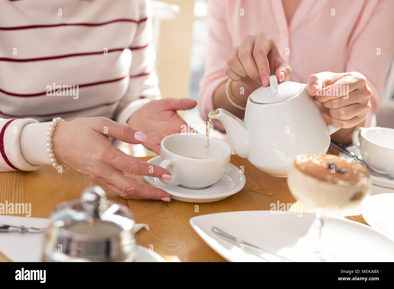 Caring girl having lunch with her granny - Stock Image