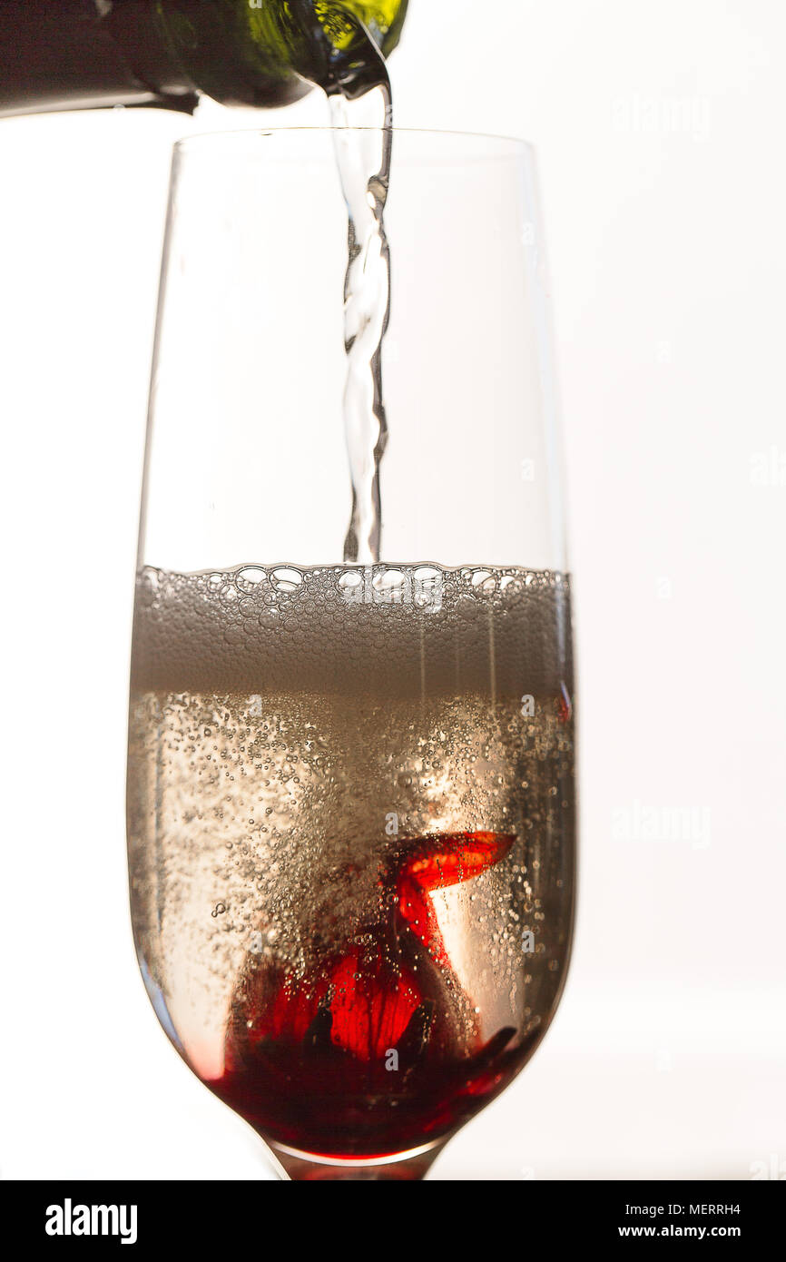 Pouring Sparkling White Wine Over Hibiscus Flower In Glass Stock