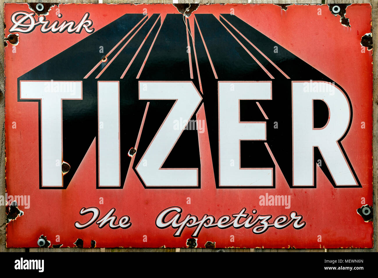 An old metal advertising sign - dates from about 1920. Tizer soft drinks. - Stock Image