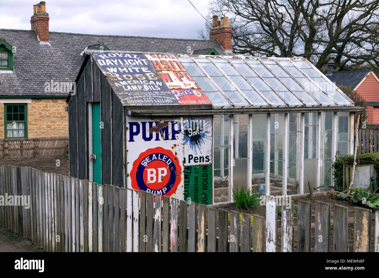 A greenhouse repaired using old metal advertising signs - northeast England. - Stock Image