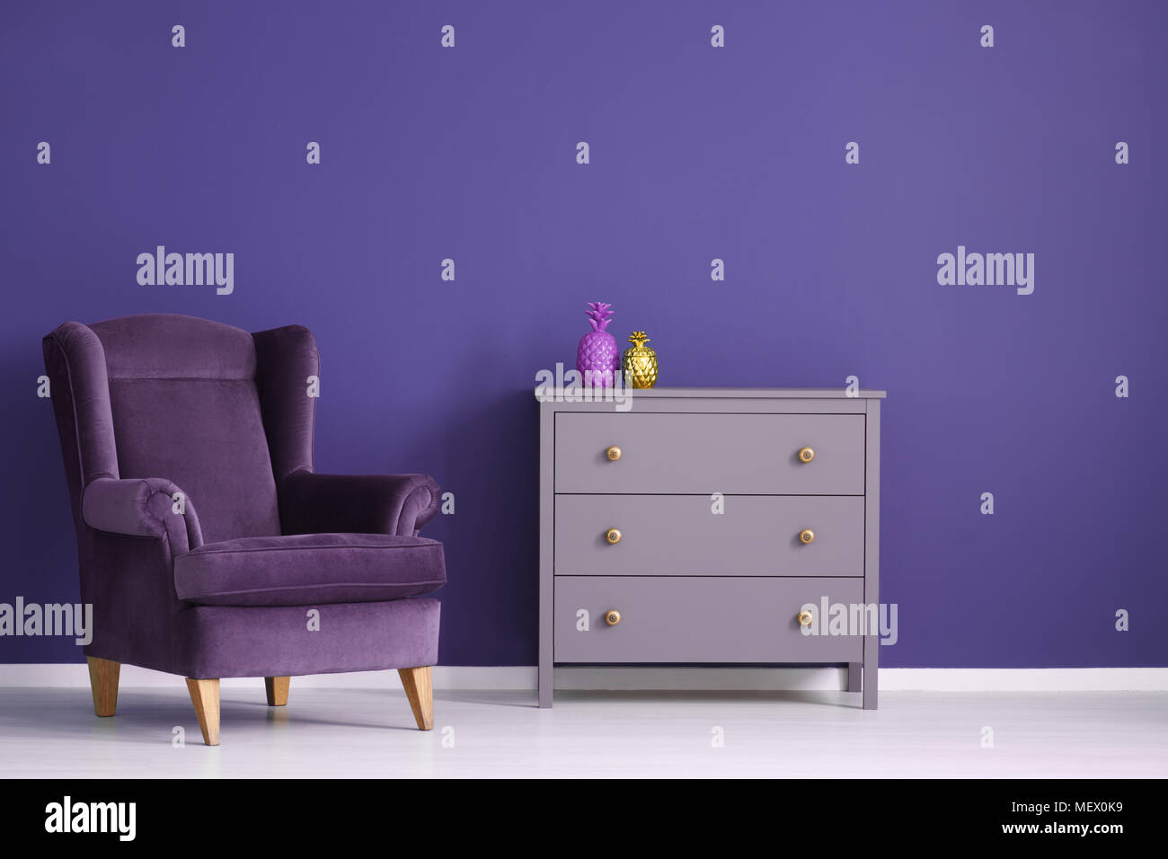 Gold Pineapple On Violet Cabinet Next To A Velvet Purple Armchair In Living  Room Interior