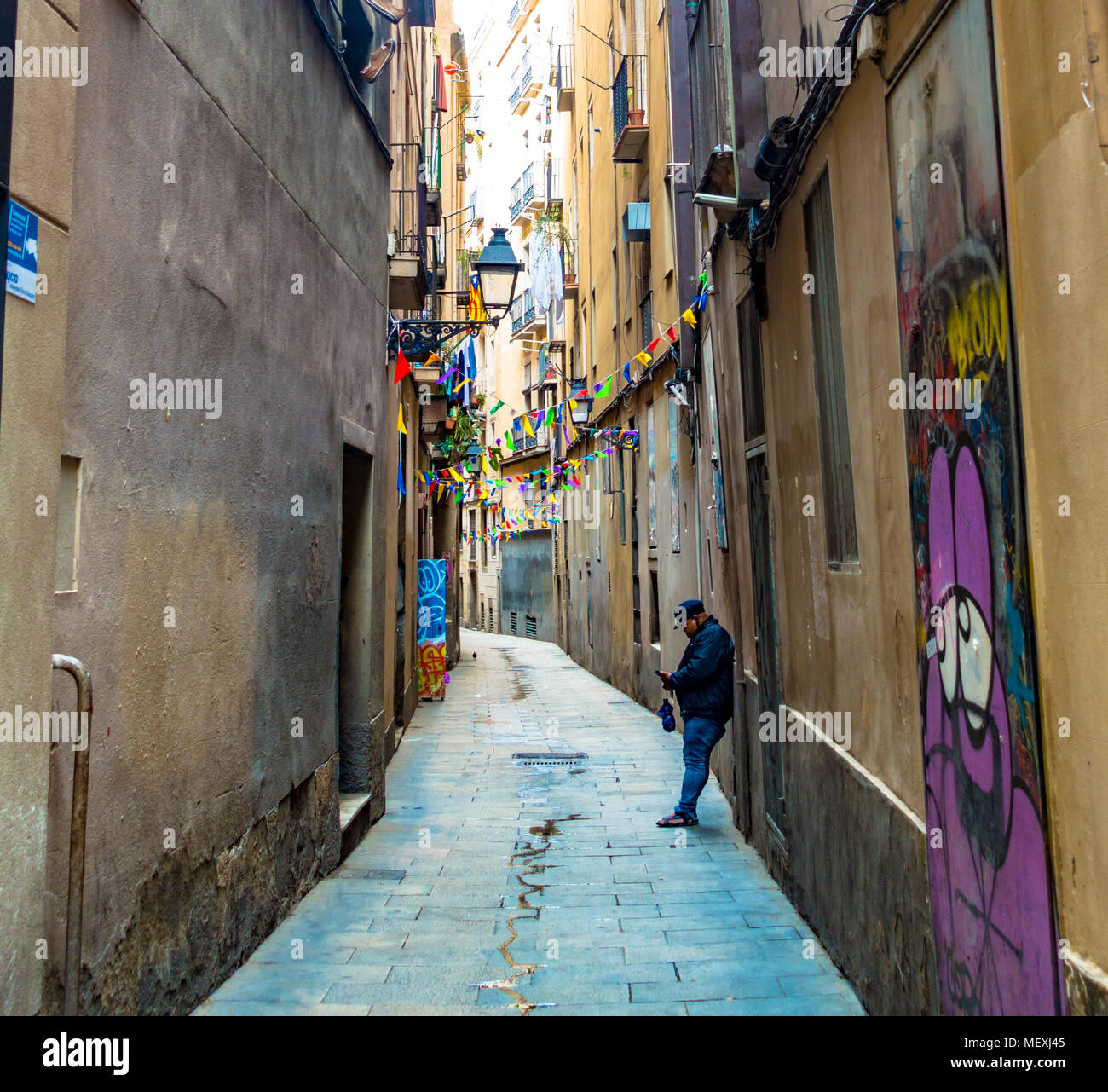 a-man-leans-against-a-wall-down-a-narrow-road-in-the-gothic-quarter-of-barcelona-to-check-his-mobile-phone-MEXJ45.jpg