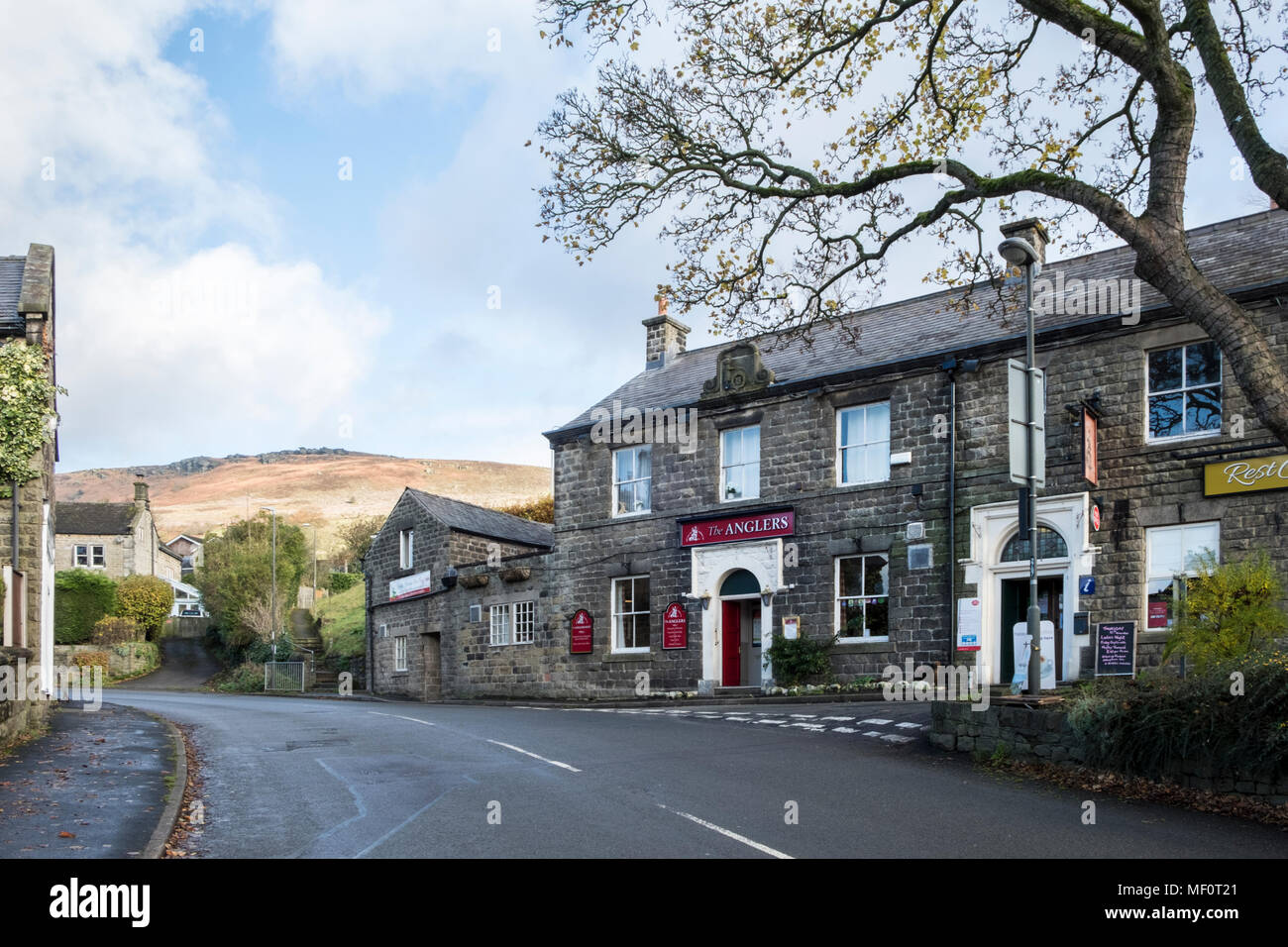 The Anglers pub in the village of Bamford with Bamford Edge in the distance rising above the village, Derbyshire, Peak District, England, UK - Stock Image