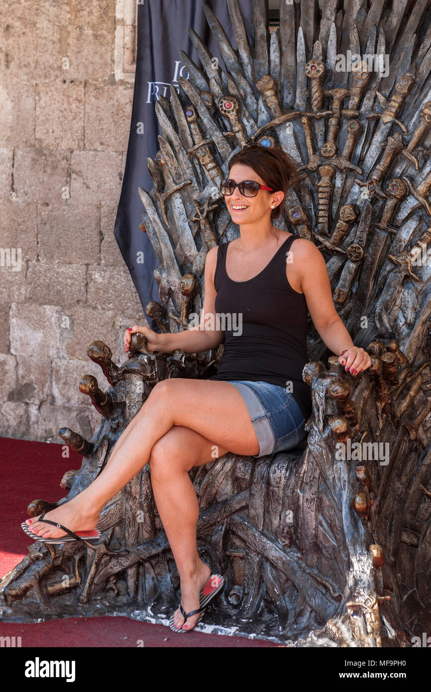 Woman sits on the Iron Throne (from the Game of Thrones), Sponza Palace, Dubrovnik, Croatia - Stock Image